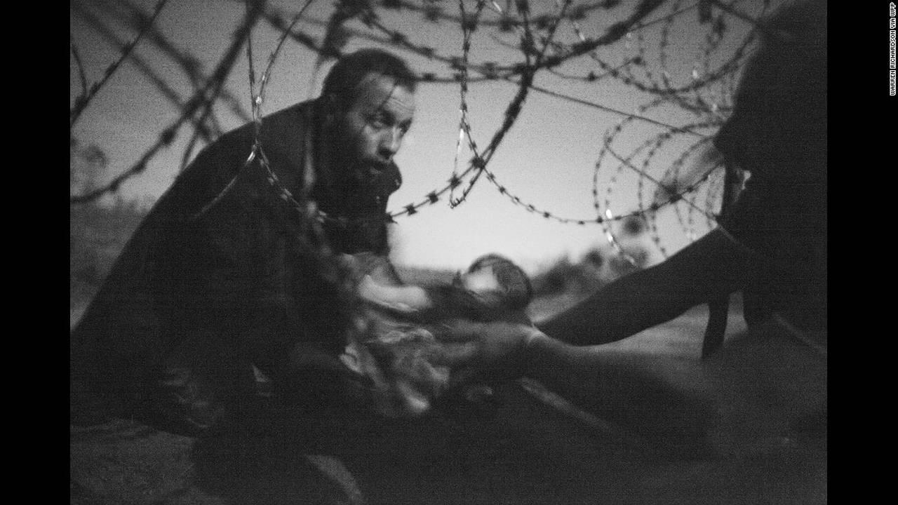 """Hope for a New Life"" (Ελπίδα για μια νέα ζωή) από τον Warren Richardson. Ένας άντρας περνάει ένα βρέφος από το φράχτη στα Σέρβο-ουγγρικά σύνορα στις 28 Αυγούστου. Η φωτογραφία κέρδισε πρώτη θέση στη κατηγορία Spot News για μονές φωτογραφίες."