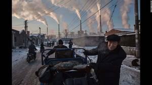 """China's Coal Addiction"" (Η εξάρτηση της Κίνας από το κάρβουνο) από τον Kevin Frayer: Κινέζοι άντρες σέρνουν ένα τρίκυκλο δίπλα σε ένα εργοστάσιο ηλεκτρισμού που δουλεύει με άνθρακα στο Shanxi της Κίνας, στις 26 Νοεμβρίου."