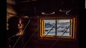 """An Antarctic Advantage"" (Ένα πλεονέκτημα στην Ανταρκτική) από τον Daniel Berehulak. Ένας ιερέας κοιτάζει έξω απο το παράθυρο μετά απο μια αγρυπνία στο Fildes Bay της Ανταρκτικής, στις 3 Δεκεμβρίου. Η ιστορία επικεντρώνεται σε μελετητές απο την Χιλή, την"