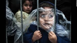 """Waiting to Register"" (Περιμένοντας για εγγραφή) από τον Matic Zorman. Το πρόσωπο ενός κοριτσιού είναι σκεπασμένο με ένα αδιάβροχο ενώ περιμένει να εγγραφεί σε στρατόπεδο προσφύγων στο Presevo της Σερβίας, στις 7 Οκτωβρίου."