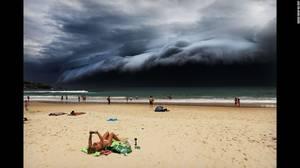 """Storm Front on Bondi Beach"" (Μέτωπο καταιγίδας στη παραλία Bondi) από τον Rohan Kelly. Ένα γιγάντιο σύννεφο πλανάται πάνω απο την παραλία Bondi στο Σίντνεϊ ενώ μια λουόμενη συνεχίζει να διαβάζει στις 6 Νοεμβρίου."