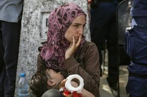 Μια μητέρα έχει το παιδί της στην αγκαλιά. Βρίσκονται στην Ειδομένη. Τα σύνορα με την ΠΓΔΜ  παραμένουν κλειστά, ενώ μια ομάδα προσφύγων ήδη έχει προσπαθήσει να ρίξει τον φράχτη.