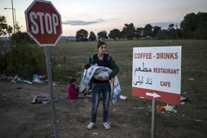 Η Χανάν, 21 ετών, έχει στην αγκαλιά της την ανιψιά της. Βρίσκονται στα σύνορα των Σκοπίων και περιμένουν να περάσουν στη χώρα.