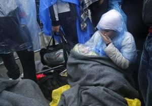 Σε μια βροχερή μέρα, μια γυναίκα έχει καλύψει το παιδί της με πλαστικό, όσο περιμένουν να περάσουν τα σύνορα της Σλοβενίας.