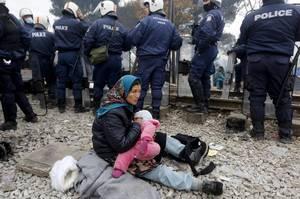 Μια μητέρα προστατεύει το παιδί της καθώς περιμένει να περάσει τα σύνορα των Σκοπίων. Μπροστά της βρίσκονται οι δυνάμεις ασφαλείας.