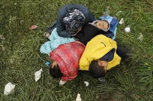 Τρία παιδιά και μια μητέρα ξεκουράζονται στη Σλοβενία, περιμένουν να περάσουν στην Κροατία.