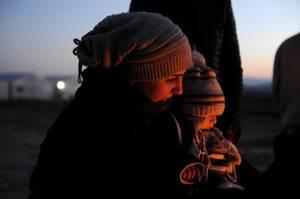 Ιδωμένη. Δίπλα σε μια φωτιά περιμένει να διασχίσει τα κλειστά σύνορα των Σκοπίων. Στην αγκαλιά της έχει ένα μωρό.
