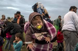 Μετανάστρια από τη Συρία με ένα μωρό στην αγκαλιά, μόλις πέρασε στην Ουγγαρία.