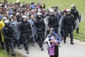 Η Φατίμα από τη Συρία, ακολουθείται από αστυνομική συνοδεία και πολλούς ακόμα πρόσφυγες καθώς διανύουν με τα πόδια τα σύνορα Κροατίας-Σλοβενίας.