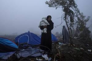 Μια πρόσφυγας έχει στην αγκαλιά της παιδί της. Βρίσκονται σε ένα χωριό της Σερβίας και αναμένεται να περάσουν τα σύνορα της Κροατίας.