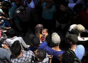 Σύριοι δημιουργούν ένας ασφαλές πέρασμα σε μια μητέρα που έχει στα χέρια της ένα μωρό. Βρίσκονται στην Κω, σε ένα στάδιο.