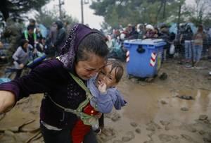 Ιδωμένη. Μια μητέρα κλαίει με το παιδί στα χέρια, μέσα στη βροχή γιατί θέλει να διασχίσει τα σύνορα.