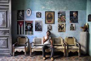 Μπροστά από ένα τοίχο γεμάτο εικόνες, στην Αβάνα της Κούβας
