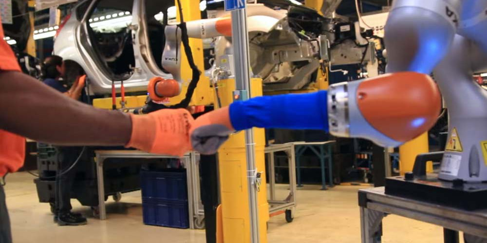 CAR WORKERS BUDDY UP WITH ROBOTS MAN AND MACHINE WORK HAND IN HAND AS FORD APPLIES INDUSTRY 1