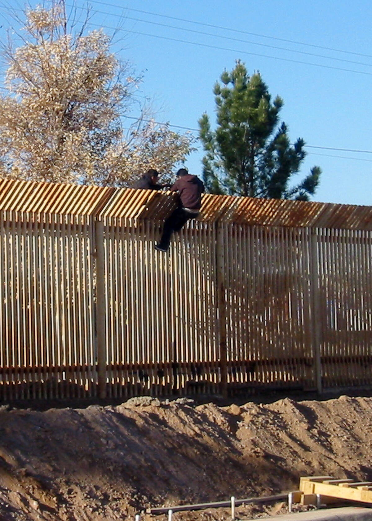 US Navy 090317 N 5253T 016 Two men scale the border fence into Mexico a few hundred yards away from where Seabees from Naval Mobile Construction Battalions NMCB 133 and NMCB 14 are building a 1500 foot long con