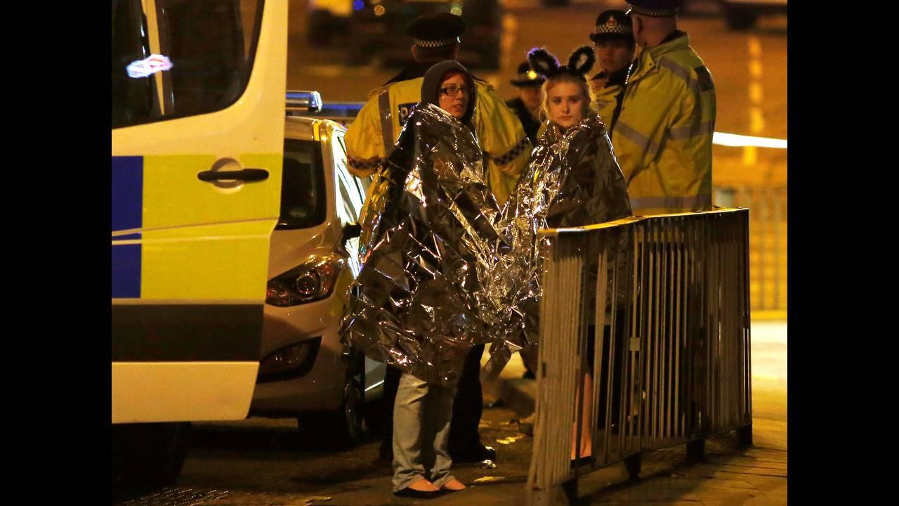 Δύο γυναίκες είναι τυλιγμένες με εσωθερμικές κουβέρτες έξω από το Manchester Arena