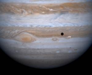"""Ο """"τερατώδης"""" πλανήτης Δίας και η Ιώ, ένας από τους τέσσερις δορυφόρους πλανήτες του."""