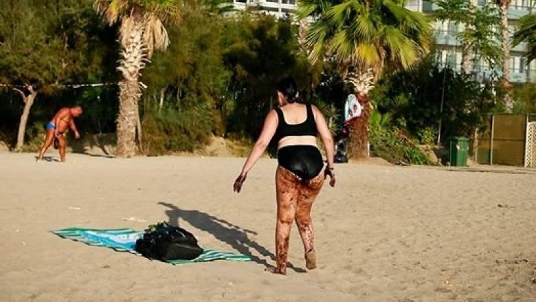 Η φωτογραφία που συγκλονίζει: Λουόμενη βγαίνει από τη θάλασσα του Π. Φαλήρου καλυμμένη με πίσσα