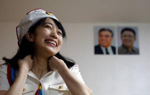 Η Τσουντσουν, πρόεδρος του φαν κλαμπ, ποζάρει μπροστά από τα πορτρέτα μελών της δυναστείας των Κιμ.