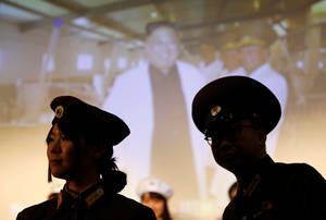 Μέλη του φαν κλαμπ, φορώντας στρατιωτικές στολές της Βόρειας Κορέας, με φόντο το πορτρέτο του Κιμ Γιονγκ Ουν.