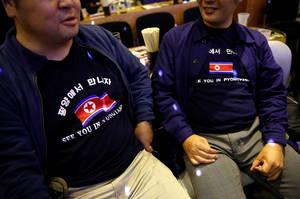 Μπλούζες με τη σημαία της Βόρειας Κορέας φορούν τα μέλη του κλαμπ κατά τη διάρκεια εκδήλωσης.