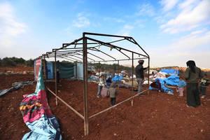 Αυτή η οικογένεια Σύρων φτιάχνει μια αυτοσχέδια σκηνή σε ένα χωράφι κοντά στα σύνορα με την Τουρκία. Το χωράφι ανήκει σε έναν αγρότη, που τους το νοικιάζει για 165 δολάρια τον μήνα. Καθώς δεν υπάρχει οργανωμένος καταυλισμός για να μείνουν, η οικογένεια δε