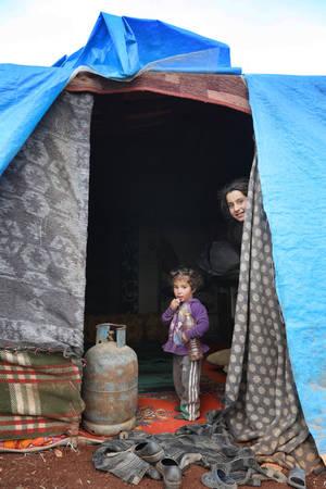 Δύο παιδιά κοιτάζουν έξω από την αυτοσχέδια σκηνή που είναι το νέο τους σπίτι. Οι κουβέρτες και το νάιλον είναι η μόνη προστασία που έχουν από το κρύο του χειμώνα. Έχουν μια μπουκάλα υγραερίου για να ζεσταίνονται, όμως δεν είναι ασφαλής η χρήση της μέσα σ