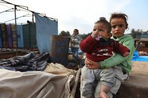 Αυτά τα παιδιά μόλις έφτασαν στο νέο τους σπίτι, μια αυτοσχέδια σκηνή που δεν είναι έτοιμη ακόμη, αλλά θα στεγάζει την οικογένειά τους επ' αόριστον. Οι οικογένειές τους εγκατέλειψαν τα σπίτια τους εξαιτίας της κλιμάκωσης των συγκρούσεων στη βορειοδυτική Σ
