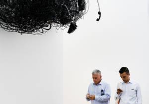 Δύο άνδρες κοιτάζουν τα κινητά τηλέφωνά τους ενώ στέκονται κάτω από ένα γλυπτό της ενσύρματης τηλεφωνίας σε έκθεση έργων τέχνης στο νησί Ράνταλ της Νέας Υόρκης. ΗΠΑ 3 Μαΐου 2018.