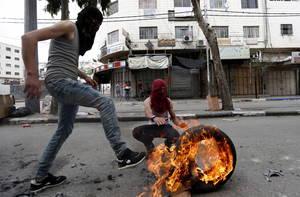 Παλαιστίνιοι κλείνουν το δρόμο με καμένα λάστιχα κατά τη διάρκεια επεισοδίων κατά του Ισραηλινού στρατού στη Δυτική Όχθη. 3 Μαΐου 2018.