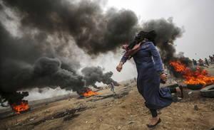 Μια γυναίκα από την Παλαιστίνη ρίχνει πέτρες κατά τη διάρκεια επεισοδίων στα ανατολικά της Γάζας μεταξύ Ισραηλινού στρατού και συγκεντρωμένων Παλαιστινίων. Γάζα 5 Μαΐου 2018.