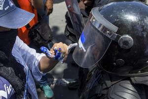 Ένας διαδηλωτής ζωγραφίζει με τα εθνικά χρώματα της Νικαράγουα το κράνος ενός αστυνομικού κατά τη διάρκεια διαδήλωσης για τα θύματα αστυνομικής βίας στην πρωτεύουσα Managua. Νικαράγουα 2 Μαΐου 2018.