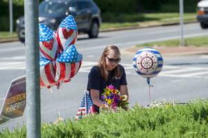 Μια γυναίκα αφήνει λουλούδια στο μνημείο των θυμάτων επίθεσης στην εφημερίδα The Capital κοντά στο γραφείο της εφημερίδας Αννάπολη του Μέριλαντ, στις ΗΠΑ, στις 29 Ιουνίου 2018.