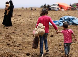 Δυο εκτοπισμένα παιδιά από την επαρχία Ντέρα περπατούν χέρι χέρι κοντά στα κατεχόμενα από το Ισραήλ υψίπεδα του Γκολάν στην Κουνιίτρα της Συρίας, 29 Ιουνίου 2018.