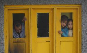 Δύο κορίτσια από το Κασμίρ και ένας άνδρας, παρακολουθούν από το παράθυρο, καθώς χωρικοί καθαρίζουν τα συντρίμμια ενός σπιτιού που υπέστη ζημιές κατά τη διάρκεια πυροβολισμών στο χωριό Kundalan, Shopian, περίπου 60 χλμ. Νότια του Srinagar, πρωτεύουσα του