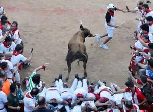 """Ενας ταύρος που εισέρχεται στην αρένα ταυρομαχιών, περνάει πάνω από τους ανθρώπους που φεύγουν προς την πύλη μετά από """"το τρέξιμο των ταύρων"""" στο πλαίσιο του Φεστιβάλ San Fermin 2018 στην Παμπλόνα, Ισπανία, 11 Ιουλίου 2018."""