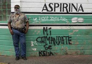 Ένας άνδρας με το πρόσωπό του καλυμμένο δίπλα σε έναν τοίχο με γκράφιτι που αναφέρει: «Ο διοικητής μου μένει», στη Ντιριάμπα της Νικαράγουα, στις 09 Ιουλίου 2018.