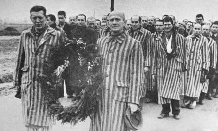 Κρατούμενοι του Άουσβιτς κρατούν ένα στεφάνι στη μνήμη των νεκρών τους. Η φωτογραφία τραβήχτηκε από Σοβιετικούς που απελευθέρωσαν το στρατόπεδο συγκέντρωσης.