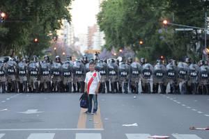 Ένας οπαδός της Ρίβερ Πλέιτ στέκει μπροστά από τις παρατεταγμένες αστυνομικές δυνάμεις πριν τον δεύτερο τελικό του Copa Libertadores μεταξύ της Μπόκα Τζούνιορς και της Ρίβερ Πλέιτ, που αποδείχθηκε δύσκολο τεστ για τους διοργανωτές και την αστυνομία. Ο εν