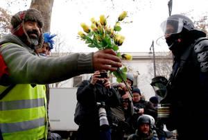 Διαδηλωτής των «κίτρινων γιλέκων» στη Γαλλία, προσφέρει λουλούδια σε αστυνομικό.