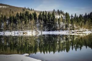 Η μαγευτική αντανάκλαση της λίμνης Πλαστήρα με το τοπίο γύρω της να έχει «ντυθεί» στα λευκά.