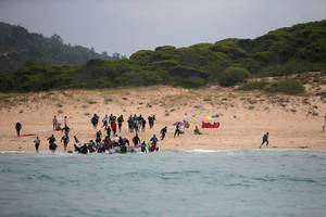 Περίπου 30 μετανάστες, καταδιωκόμενοι από σκάφος της αστυνομίας, οδήγησαν τη φουσκωτή τους λέμβο σε μια ισπανική παραλία και έπειτα διασκορπίστηκαν στους γύρω αμμόλοφους και το δάσος. (27 Ιουλίου 2018)