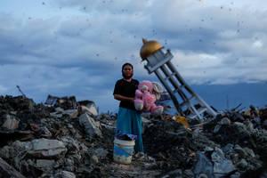 Μια γυναίκα κρατά στην αγκαλιά της ένα λούτρινο λαγουδάκι, στα συντρίμμια του σπιτιού της, όπου έχασε τα τρία της παιδιά στο Παλού, στην Ινδονησία, μετά από φονικό τσουνάμι. (7 Οκτωβρίου 2018).