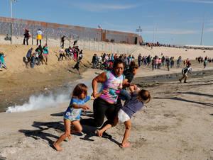 Η Μαρία Μέζα, μια 40χρονη μετανάστρια από την Ονδούρα, κρατώντας σφικτά τις δύο πεντάχρονες κόρες της προσπαθεί να ξεφύγει από τα δακρυγόνα που ρίχνουν Αμερικανοί στρατιώτες στα σύνορα με το Μεξικό στην Τιχουάνα, από όπου ήθελε να περάσει. (25 Νοεμβρίου 2