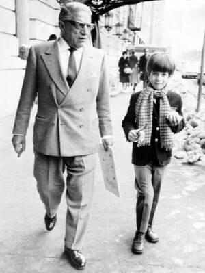 1969 Ο Τζον Κένεντι, γιος της Τζάκι Ωνάση και του Τζακ Κένεντι, συνοδεύει τον πατριό του, Αριστοτέλη Ωνάση, στο εστιατόριο Trader Vic's, στη Νέα Υόρκη.