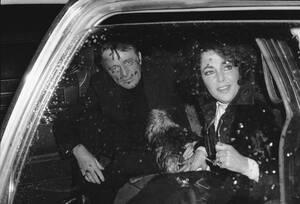 1976 Η Ελίζαμπεθ Τέιλορ και  σύζυγός της Ρίτσαρντ Μπάρτον φεύγουν από το αεροδρόμιο της Νέας Υόρκης. Η Τέιλορ έχει μόλις καταφτάσει από τη Γενεύη, απ' όπου έφερε και το σκύλο.