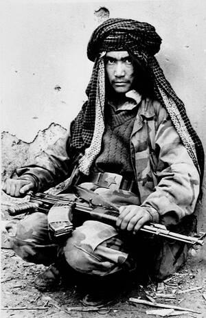 1989 Φορώντας τη ζώνη ενός αιχμάλωτου Σοβιετικού στρατιώτη, ένας Αφγανός αντάρτης ακουμπάει σε έναν τοίχο διάτρητο από βολές. Είναι μόλις 13 ετών και μέλος μιας επίλεκτης μονάδας ανταρτών που κατάφερε να διεισδύσει στην πόλη Γκάνζι.