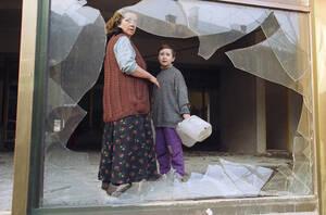 1993 Μια Βόσνια γυναίκα και ο γιος της στέκονται πίσω από ένα σπασμένο παράθυρο σε ένα κτήριο που δέχθηκε την επίθεση ελεύθερων σκοπευτών στο Σαράγιεβο το 1993. Κάποιες περιοχές της πόλης είναι χωρίς νερό και ρεύμα. Καθ' όλη τη διάρκεια της ημέρας η πόλη