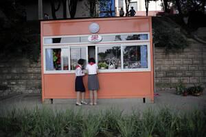 Στο δρόμο από το σχολείο στο σπίτι, δύο κορίτσια σταματούν σε ένα κιόσκι για να αγοράσουν λουλούδια.