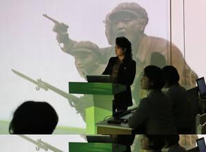 """Στην Παιδαγωγική Σχολή της Πιονγιάνγκ, μια καθηγήτρια διδάσκει, ενώ πισω της """"τρέχουν"""" εικόνες από την επανάσταση."""